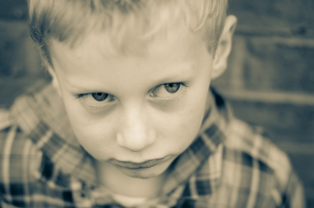 zoomed in: young boy sulking pouting monochrome