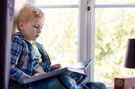 young child reading a book on a window seat at home photo