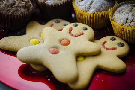 3 smiling happy gingerbread men with orange and yellow buttons on red metalic Christmas plate with muffins