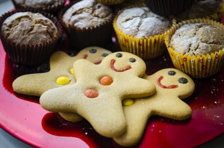 baked goods: 3 smiling happy gingerbread men with orange and yellow buttons on red Christmas metalic plate with muffins and dusted with icing sugar side view