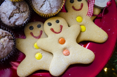 3 smiling happy gingerbread men with orange and yellow buttons on red Christmas metalic plate with muffins and dusted with icing sugar