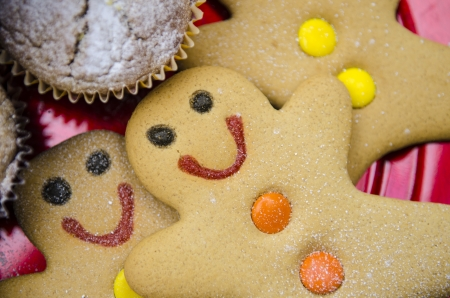 smiling gingerbread men with orange and yellow buttons on red Christmas metalic plate Stock Photo