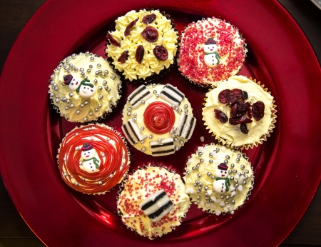 Christmas cupcakes with buttercream sweets, candy, liquorice and cranberries on metalic red plate