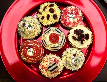 Christmas cupcakes with buttercream sweets, liquorice,candy and cranberries on metalic red plate BRIGHT