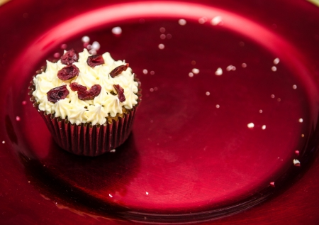 Christmas spiced muffin topped with buttercream and cranberries on a red metalic festive plate, the last one with crumbs