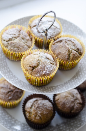 Spiced pumpkin muffins in yellow cases on a white cake stand Stock Photo
