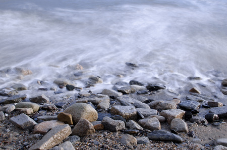 spring tide: Long exposure capture of the ocean lapping over rocks during high tide at Charlestown, Cornwall (UK).