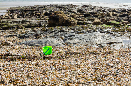 left behind: A childs green bucket lays abandoned on a pebble beach.