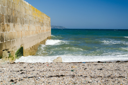 pebble beach: Seascape image with pebble beach, harbor wall breakwater, lighthouse in the distance and blue sky Stock Photo