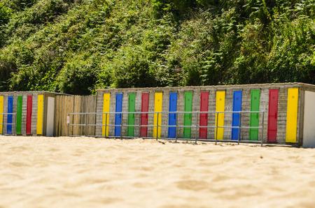 beach huts: A row of colorful beach huts on the edge of a sandy beach