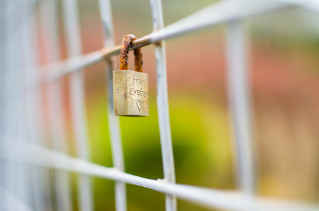 shallow  focus: A closed metal padlock is locked onto a section of square fence. Etched onto the padlock is from Exeter with shallow focus  short depth of field
