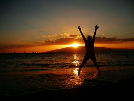 Silhouetted girl on the beach, jumping in the ocean with sunset in background Stock Photo