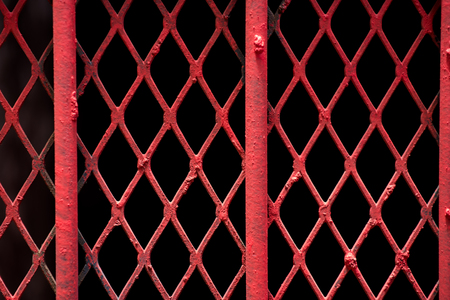 An abstract shot of fine red painted wire lattice on a barred window in Johannesburg inner city