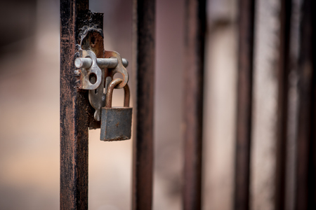 An abstract style closeup of a rusty padlock on a iron barred gate in Johannesburg CBD