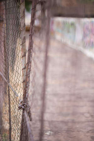 An abstract style shot of shoddy wire mesh fencing and gates with graffiti in the background in Johannesburg inner city