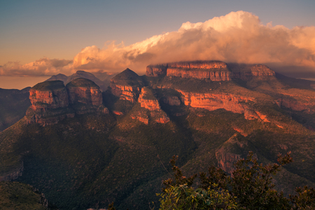The Three Rondavels glowing hot pink red under a golden blanket of cloud in the intense light of sunset. Mpumalanga, South Africa