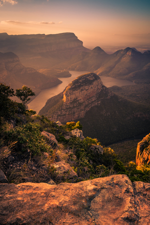 Portrait Shot of Blyde River Canyon bathed in dreamy warm pinks and oranges during pre-sunset golden hour. Foreground Rock. Mpumalanga, South Africa Imagens