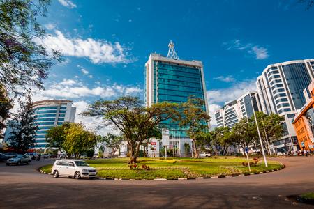 Kigali, Rwanda - 21 septembre 2018 : Une voiture passe le rond-point du centre-ville, avec Pension Plaza et les bâtiments environnants en arrière-plan