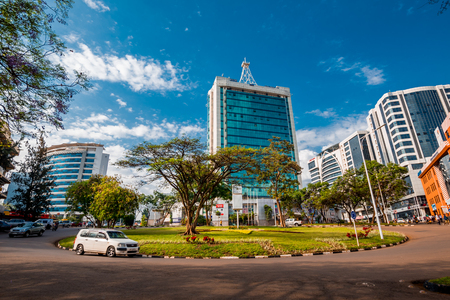 Kigali, Rwanda - September 21, 2018: A car passes the city centre roudabout, with Pension Plaza and surrounding buildings in the background