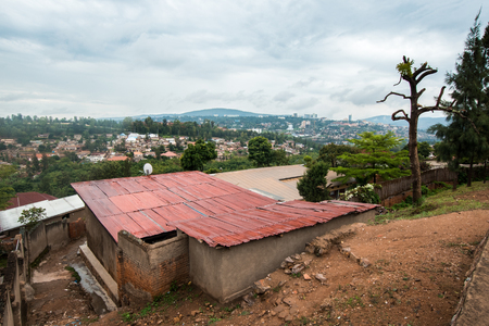 Kigali, Rwanda - September 20, 2018: A shabby concrete house in the foreground, with the Kigali skyline on a distant hill 에디토리얼