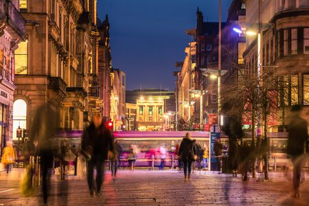 Glasgow / Scotland - February 15, 2019: Pedestrians walking along the brightly lit Buchanan street in the city centre at night