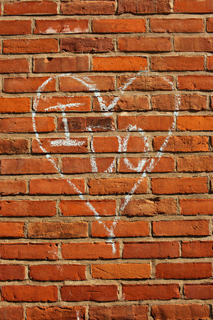 I Do and heart written in chalk on red brick wall