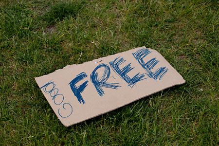 Free handwritten sign on cardboard against green grass Фото со стока