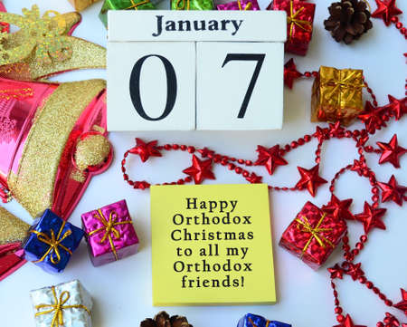 Text label and cube 7th January with Christmas ornament background. Orthodox Christmas Concept