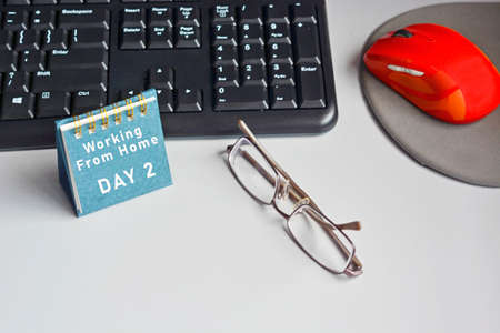 Home desk with keyboard, mouse, eyeglasses and calendar with text. Working from home concepts Archivio Fotografico