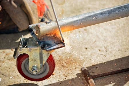 Worker with a welding machine fixing a caster wheels with fiery sparks flying around