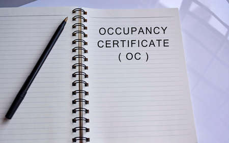 Occupancy certificate text written on a notepad with a pen on white table