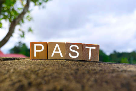 Past text on wooden cube block on top of big stone with blurred sky background