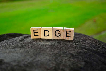 Edge text on wooden cube block on top of big stone with blurred green background