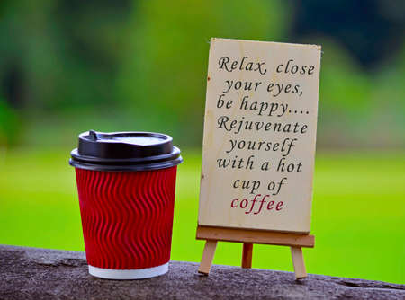 Red paper cup of coffee with text written on chalkboard and greenery background