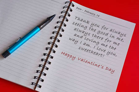 Text on white notepad with red background. Top view and Valentine's day concept