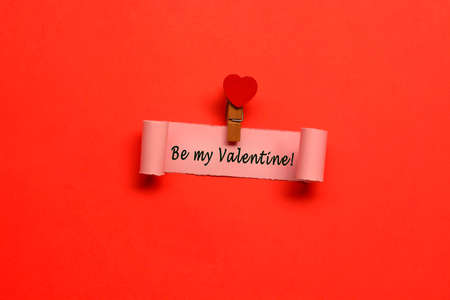 Be my Valentine label on torn paper with red paper background. Valentine's Day concept