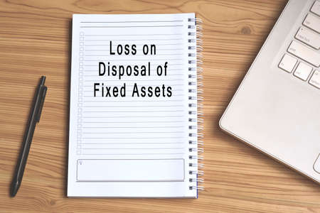 Loss on disposal of fixed assets label on notepad with laptop and smartphone on wooden table. Business concept
