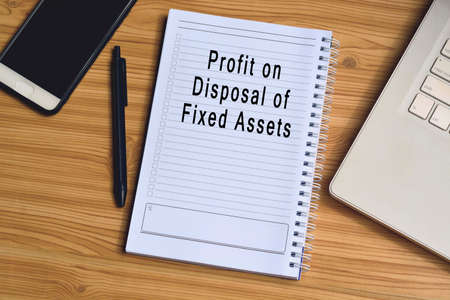 Profit on disposal of fixed assets label on notepad with laptop and smartphone on wooden table. Business concept
