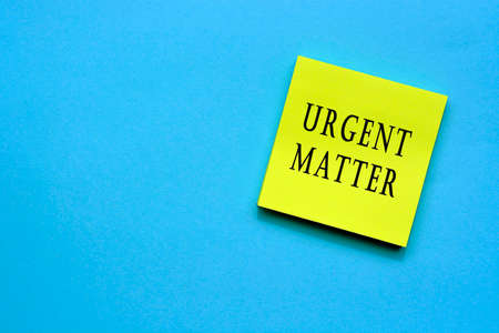 Urgent matter text on yellow sticky note with blue background