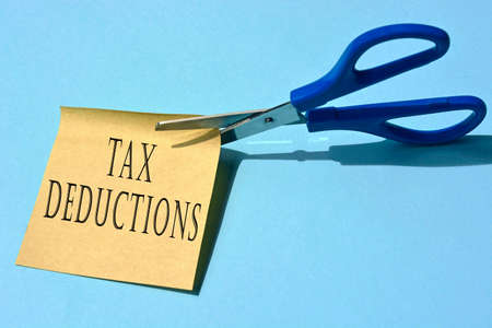 Scissors that cut yellow notepad with tax deductions text on a blue background. Tax concept