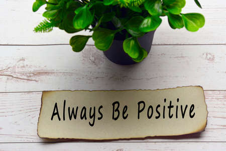 Motivational and inspirational quote on burnt edge brown paper with blurred plant on wooden desk - Always be positive