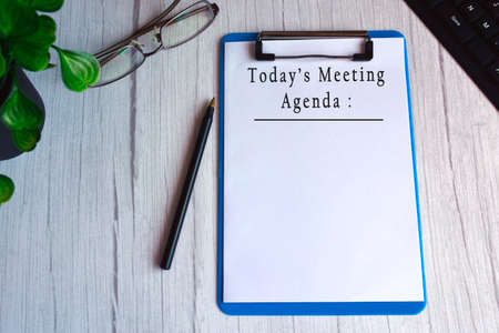 Today's meeting agenda text on blue clip board. Meeting goals concept