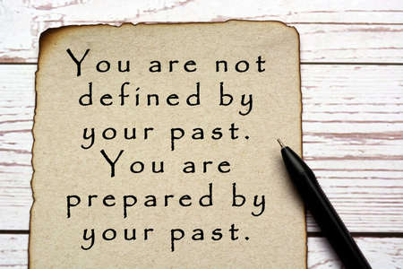 Motivational and inspirational quote on burnt edge brown paper with pen on wooden desk - You are not defined by your past, you are prepared by your past.