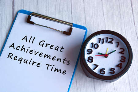 Motivational and inspirational quote on blue clip board with alarm clock on wooden desk - All great achievements require time Banque d'images