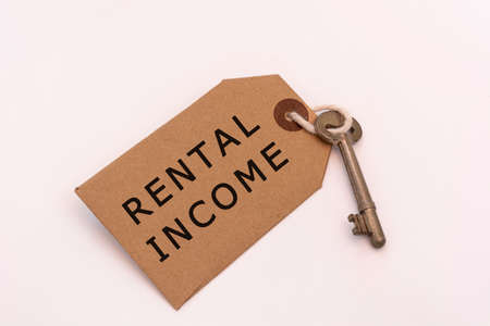 Text on a brown tag with key on white background - Rental income