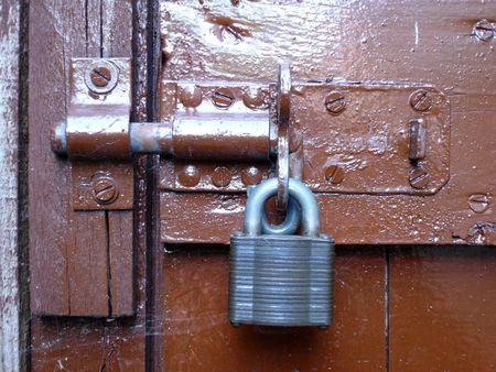 Bolted door with grey metal padlock photo