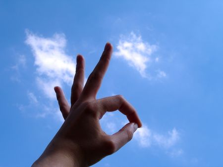 Ok Sign (hand sign) with cloud background Stock Photo