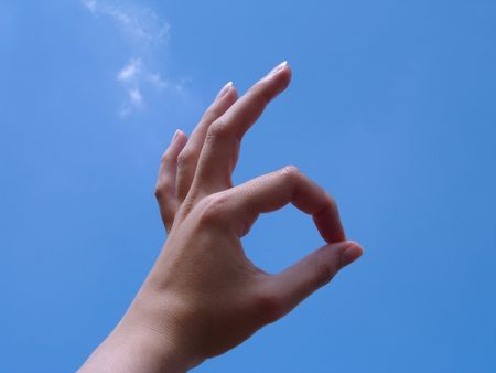 Ok Sign (hand sign) with sky background