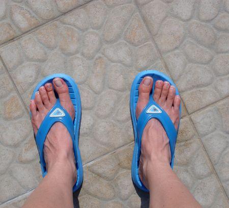 Blue flip-flops worn on feet