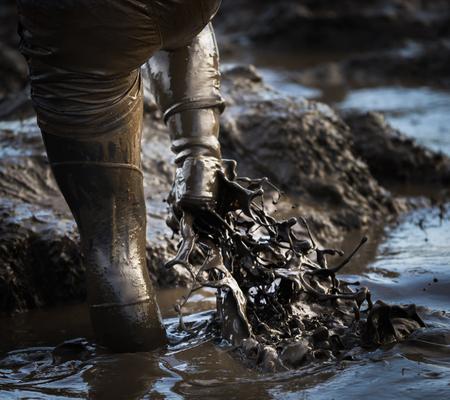 Modder modder glous modder. Modderige voeten spatten door diep water en modder in een race